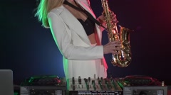 Young sexy, blonde woman dj in white jacket playing music using saxophone on Arkistovideo