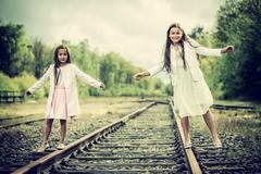 Two sisters walking on a rail Stock Photos