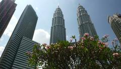Pan shot flowering tree against Menara Petronas skyscrapers, high angle view Stock Footage