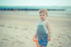 Little child boy is upset on the beach because of his wet shirt Stock Photos