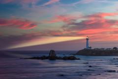 Lighthouse with light beam at sunset Stock Photos
