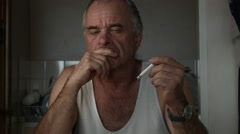 Adult male holding cigarette attempting to quit smoking at table Stock Footage