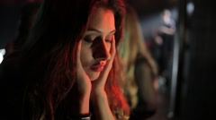 Beautiful woman sitting alone at bar counter in night club Stock Footage