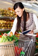Buying goods in supermarket - stock photo