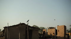 Crow next to a poor village house in India, long shot Stock Footage