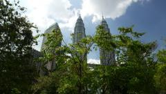 Petronas Twin Towers view through green trees crown, panning shot Stock Footage