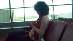 Woman brawse internet on smartphone waiting for plane departure. 4K uhd stock Stock Footage