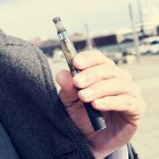 Man vaping with an electronic cigarette outdoors Stock Photos