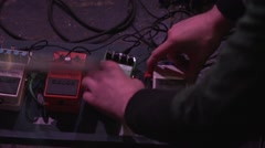Musician arranging effect pedal on stage in night club Stock Footage