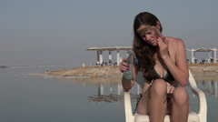 Woman enjoying the natural mineral mud sourced from the Dead Sea Israel Stock Footage