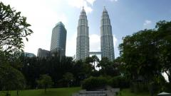 Petronas Twin Towers skyline through trees, long panning shot Stock Footage