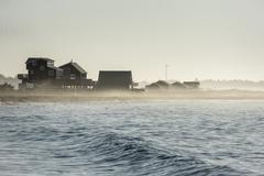 Morning mist drifting across New England beach - stock photo