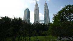 Long panning shot of beautiful Petronas Twin Towers behind park trees Stock Footage