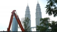 Excavator arm against Petronas Twin towers, construction digging Stock Footage