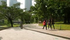 Three young indian girls walk in park, sunny day, first Petronas tower on back Stock Footage