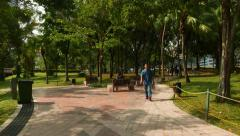 Walkways in KLCC park, rest area bench, security woman, few people Stock Footage