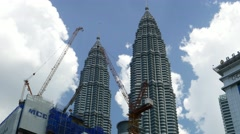 Construction site crane against Petronas Twin Towers, blue sky and clouds Stock Footage