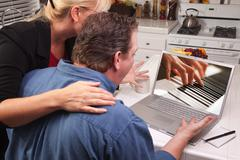 Couple In Kitchen Using Laptop with Piano Performer on the Screen. Stock Photos
