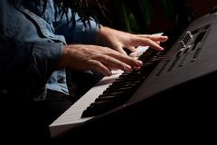 Male Pianist Performs on the Piano Keyboard with Dramatic Lighting. Stock Photos