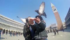 SLO MO Medium Shot couple feeding pigeons on St. Mark's Square in Venice Stock Footage