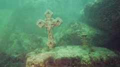 Christian stone cross under water with a stone statue of a saint - stock footage