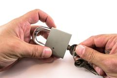 Hands Unlocking a Padlock Stock Photos