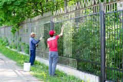 Two Workers Painting a Metal Fence - stock photo