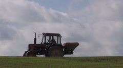 Small old agriculture tractor fertilize crop field in spring Stock Footage