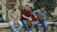 Three talented young guys playing musical instruments and sing a song  Stock Footage
