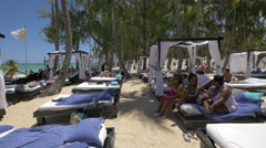 Women and men relaxing on the beach in Punta Cana, Dominican Republic Stock Footage
