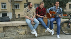 Three stylish musicians perform a musical appearance on the street Stock Footage