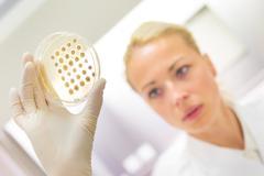 Scientist observing petri dish. - stock photo