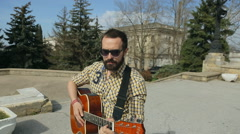 Sexy guy with a beard and glasses playing guitar on the street Stock Footage