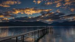 Sunset time lapse, clouds reflection at a jetty in Te Anau lake Stock Footage