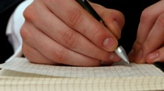 Hand writing a message in the open notebook Stock Footage