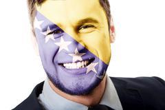 Man with Bosnia and Herzegovina flag on face. - stock photo