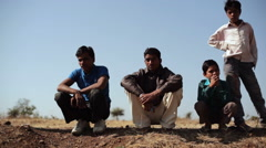 Village men and boys sitting in dry land, long shot, shallow DOF Stock Footage