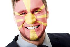Stock Photo of Happy man with Macedonia flag on face.