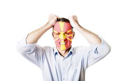Mature man with Macedonia flag on face. - stock photo
