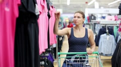 Stock Video Footage of Woman buys a t-shirt in the store