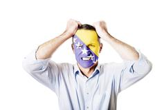 Stock Photo of Mature man with Bosnia and Herzegovina flag on face.