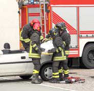 italian firefighters relieve an injured after car accident - stock photo