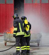 Firefighters with oxygen bottles off the fire Kuvituskuvat
