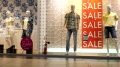 Mannequins in a showcase window of fashionable clothes shop Stock Footage