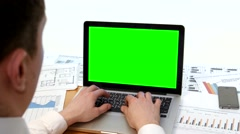 Man hand on laptop keyboard with green screen monitor in the office Stock Footage