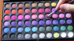 4K Brush taking some eyeshadow from a palette of multicolor makeup - stock footage