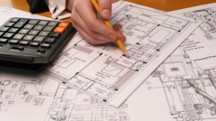 Developing engineering project. Male architect checking numbers on blueprint - stock footage