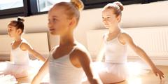 Three pretty young girls in ballet class - stock photo