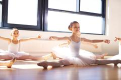 Sitting Young Ballerinas Stretching Arms and Legs - stock photo