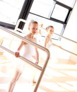 Aspiring young ballerinas practicing at the bar - stock photo
